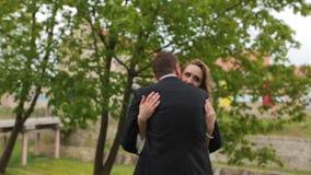 Bella sposa e sposo felici che posano vicino all'albero verde nel parco stock footage