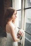 Bella sposa elegante di nozze che posa vicino al grande arco della finestra immagine stock libera da diritti