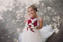 Bella sposa felice e sorridente in vestito da sposa che sta con un mazzo dei pioni in mani Immagine Stock