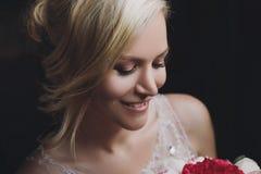 Bella sposa felice e sorridente in vestito da sposa che sta con un mazzo dei pioni in mani Immagine Stock Libera da Diritti