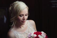 Bella sposa felice e sorridente in vestito da sposa che sta con un mazzo dei pioni in mani Fotografie Stock