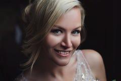 Bella sposa felice e sorridente in vestito da sposa che sta con un mazzo dei pioni in mani Fotografia Stock Libera da Diritti