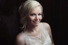 Bella sposa felice e sorridente in vestito da sposa che sta con un mazzo dei pioni in mani Fotografia Stock