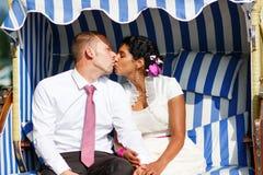 Bella sposa indiana e sposo caucasico, nella sedia di spiaggia. Fotografia Stock