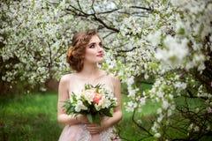 Bella sposa nel mazzo della tenuta del vestito da sposa in mani immagini stock