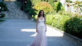 Bella sposa nelle passeggiate bianche del vestito lungo il viale stock footage