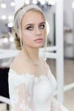 Bella sposa tenera sveglia della ragazza in vestito da sposa in specchi con i capelli di sera ed il trucco leggero delicato fotografie stock libere da diritti