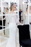 Bella sposa tenera sveglia della ragazza in vestito da sposa in specchi con i capelli di sera ed il trucco leggero delicato immagine stock