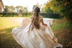Bella sposa in un vestito da sposa bianco che corre nel parco immagine stock
