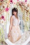Bella sposa in un vestito da sposa in un interno di eleganza in uno studio immagine stock