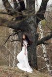 Bella sposa in vestito bianco che sta davanti all'albero grigio Immagine Stock