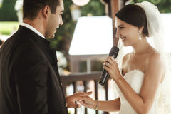 Bella sposa in vestito bianco ed in sposo bello che scambiano rin Fotografia Stock