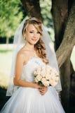 Bella sposa in vestito bianco vicino ad un albero Immagine Stock