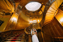 Bella sposa in vestito da sposa che tiene un mazzo sveglio con le rose rosse e bianche che posano sul fondo di sbalordire Immagine Stock Libera da Diritti