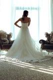 Bella sposa in vestito da sposa elegante che posa nella camera da letto, vista posteriore fotografia stock