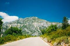 Bella strada della montagna dell'asfalto sotto cielo blu soleggiato Fotografie Stock Libere da Diritti