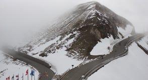 Bella strada tortuosa alla cima della montagna ed attraverso la nuvola Immagini Stock