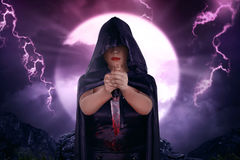 Bella strega asiatica con il mantello nero che tiene coltello sanguinoso Fotografie Stock Libere da Diritti