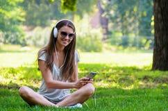 Bella studentessa alla moda snella che si siede sui gras verdi Fotografia Stock