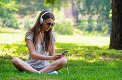 Bella studentessa alla moda snella che si siede sui gras verdi Immagini Stock Libere da Diritti