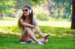 Bella studentessa alla moda snella che si siede sui gras verdi Immagine Stock Libera da Diritti