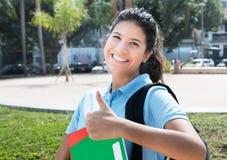 Bella studentessa caucasica che mostra pollice nella città dentro Fotografia Stock Libera da Diritti