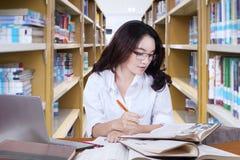 Bella studentessa che fa compito scolastico in biblioteca Fotografia Stock
