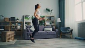 Bella studentessa che fa gli esercizi a casa che corrono sul posto nel piano video d archivio