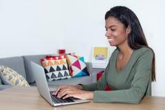 Bella studentessa che impara a casa con il computer portatile Fotografie Stock