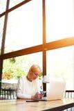Bella studentessa che si siede in un caffè con un computer Fotografie Stock