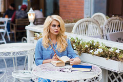 Bella studentessa con il sembrare stupefacente che prepara per le conferenze mentre sedendosi con i libri in caffè Fotografia Stock Libera da Diritti