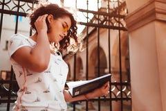 Bella studentessa di college che legge un libro all'aperto Apprendimento alla moda alla moda della studentessa Fotografia Stock