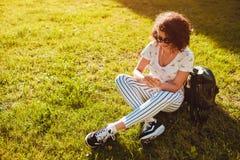 Bella studentessa di college che per mezzo dello Smart Phone ed ascoltando la musica nel parco della città universitaria fotografia stock