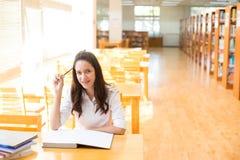 Bella studentessa di college indiana che legge un libro in biblioteca con il Se Fotografia Stock