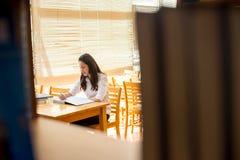 Bella studentessa di college indiana che legge un libro in biblioteca con il Se Immagine Stock