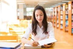 Bella studentessa di college indiana che legge un libro in biblioteca con il Se Immagini Stock