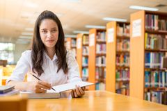 Bella studentessa di college indiana che legge un libro in biblioteca con il Se Fotografie Stock Libere da Diritti