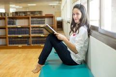 Bella studentessa di college indiana che legge un libro in biblioteca con il Se Fotografia Stock Libera da Diritti