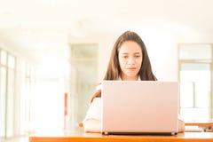 Bella studentessa di college indiana che per mezzo del computer portatile con il fuoco selettivo Fotografia Stock
