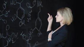 Bella studentessa, esaminante la formula chimica e graffiante la sua testa, pensante alla soluzione video d archivio