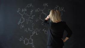 Bella studentessa, esaminante la formula chimica e graffiante la sua testa, pensante alla soluzione archivi video