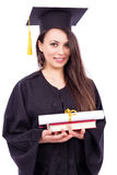 Bella studentessa nel libro e nella immersione della tenuta dell'abito di graduazione Fotografia Stock