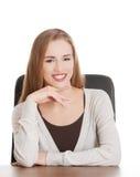 Bella studentessa sorridente casuale che si siede da uno scrittorio. Immagini Stock