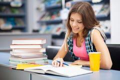Bella studentessa in una libreria Immagini Stock Libere da Diritti