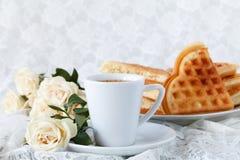 Bella tazza bianca di caffè nero e del fiore rosa su un fondo bianco Fotografia Stock