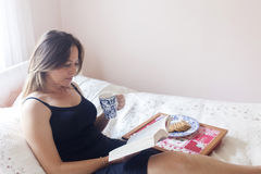 Bella tazza da caffè della tenuta del libro di lettura della donna Fotografie Stock