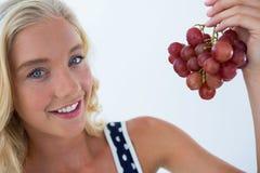 Bella tenuta della donna al mazzo di uva rossa Fotografia Stock