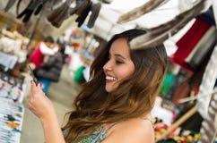 Bella tenuta sorridente della donna qualcosa in sua mano nell'abbigliamento e negli artigianato tradizionali andini con vaghi Fotografia Stock