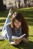 Bella ubicazione della ragazza sull'erba e sulla lettura un edu del libro Immagini Stock Libere da Diritti