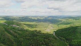 Bella valle collinosa della montagna accesa dal sole Molti foreste su terra e molto bello il cielo archivi video